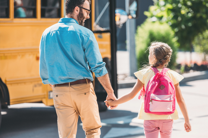 Father Daughter walking to school bus
